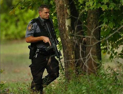 A Pennsylvania State Trooper walks in a wooded area near Route 447 in Price Township on Sunday, Sept. 21, 2014, near Canadensis, Pa., during a massive search for suspected killer Eric Frein